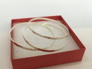 3 skinny silver bangles in a box